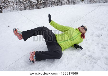 Risk of accidents in winter. Mid aged woman is slipping and falling on footpath, street covered with snow and black ice