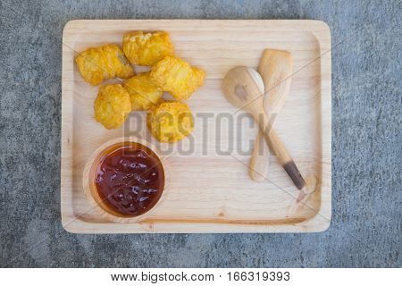 Chicken nuggets and tomato sauce on a wooden background.