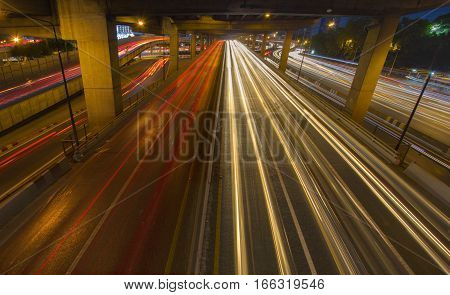 Car light trails on street highway expressway motorway through the city in rush hour. Busy Road Traffic at big junction at night