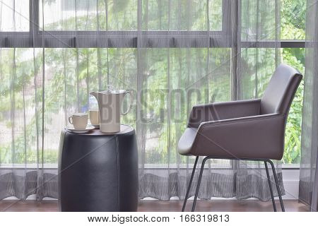 Ceramic Coffee Set On Top Of Table With Dark Brown Leather Chair