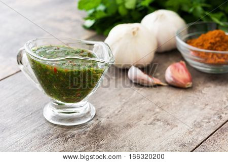 Green Chimichurri Sauce and ingredients on wooden table
