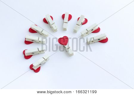 wooden clothes pin or cloth pegs with heart shape design on white background for valentine object