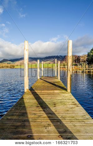 A portrait view of a wooden jetty on Derwentwater in the English Lake District.