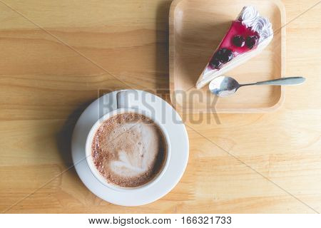 hot coffee mocha with foam milk and blueberry cake in countryside cafe