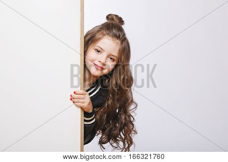 Portrait of little hipster girl looking out. Curly hairstyle. Copy-space. Studio