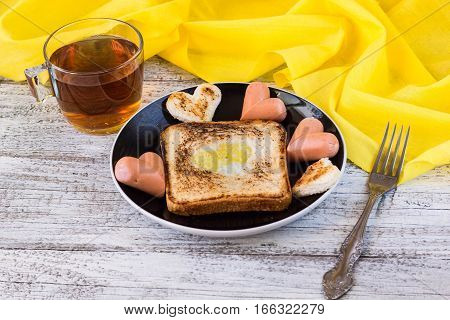 breakfast for the celebration of Valentine's day - toast with scrambled eggs in the form of hearts sausages and tea