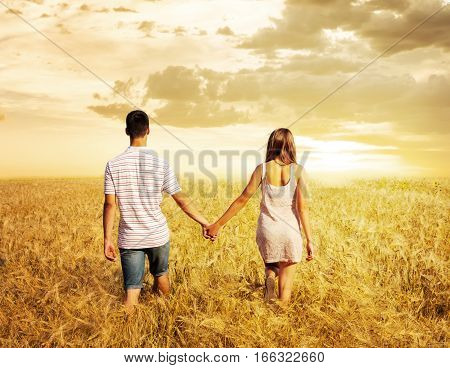 Young in love couple walking in field at sunset holding hands