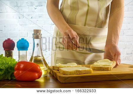 Girl preparing sandwiches and spreads butter on the bread