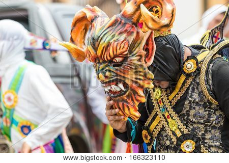 May 25 La Villa de los Santos Panama: man lifts its mask in the scorching heat walking on street wearing colourful traditional clothing during Corpus Cristi celebration