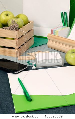 Office table with elements of corporate identity and wooden box with green apples. Blank cards paper folder and smartphone. Mock up