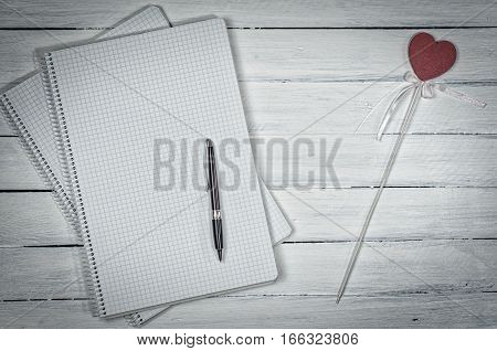 Open notebook in the small cell with a pen vintage white background