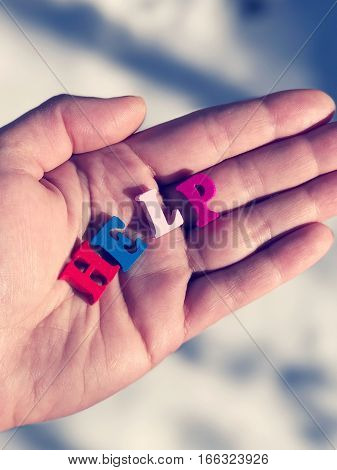 Word help of small colored wooden letters on a human hand vintage toning