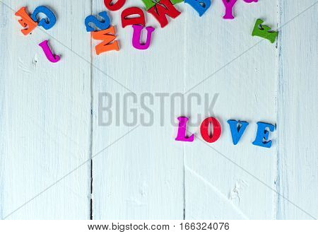 white wooden background with the word love in wooden letters