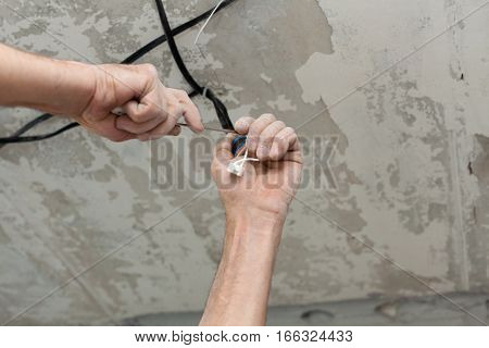 Electricians cleans the contacts with pliers. Installing the ceiling light.