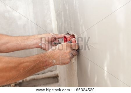 Electrician installing wall power socket, plastic electrical junction box