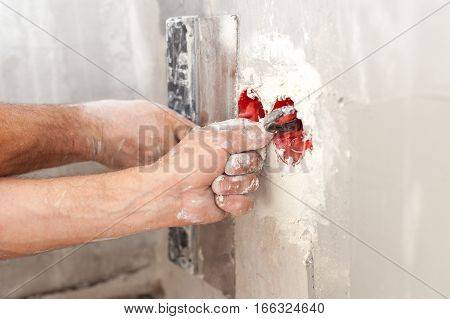 Electrician installing wall power socket plastic electrical junction box