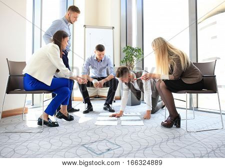 Creative people looking at project plan laid out on floor. Business associates discussing new project plan in modern office.