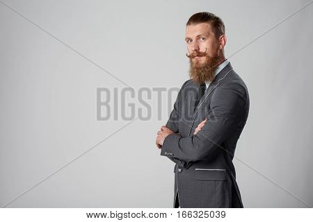Confident stylish business man in suit standing with folded hands over grey background