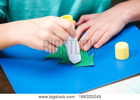 Cropped shot of child making christmas card with glue and paper