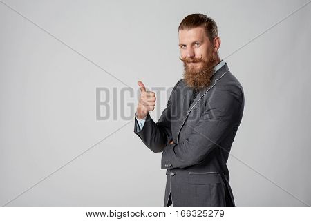Confident stylish business man in suit standing with folded hands gesturing thumb up, over grey background