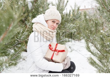 The happy young girl holds in hand a box with a New Year's gift among trees fir-trees and pines