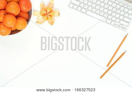 Minimal elegant desk composition flat lay with tangerine and keyboard