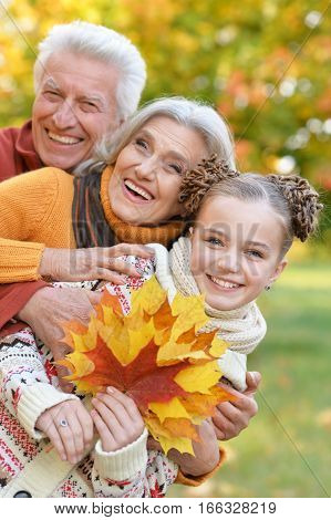 grandparents with granddaughter posing outdoors in autumn part