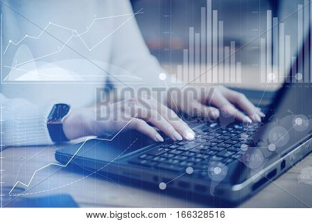 Concept of digital screen, virtual connection icon, diagram, graph interfaces.Closeup view young businesswoman working at a laptop, typing on keyboard while sitting her work place.Blurred effect
