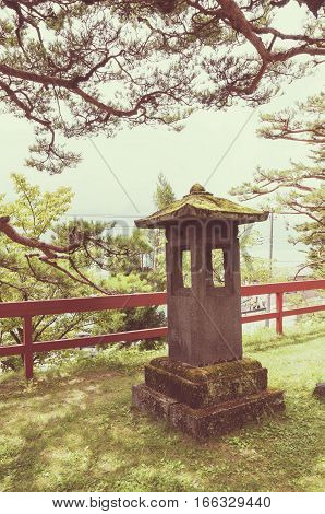 ancient Japanese stone lantern near red wooden fence