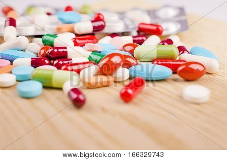 Multicolored capsules and pills lying on a wooden surface. Closeup