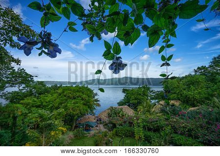The Apoyo lagoon in Nicaragua seen through lush green vegetation
