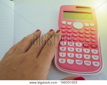 Pink Calculator On A Blank Notebook With A Hand