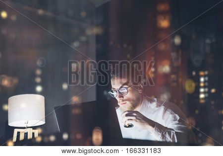 Bearded young businessman working on modern loft office at night. Man using contemporary notebook texting message, holding cup of espresso, blurred background. Horizontal, film effect, reflections