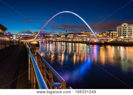 Twilight at Gateshead Millennium Bridge, on the Quayside at Newcastle on the banks of the River Tyne, and Newcastle upon Tyne skyline beyond