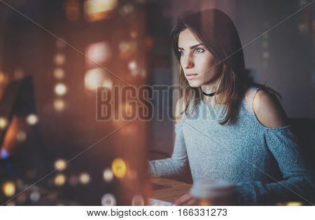Young beautiful woman working on modern loft office at night. Girl using contemporary desktop computer, blurred background. Horizontal, film effect, reflections