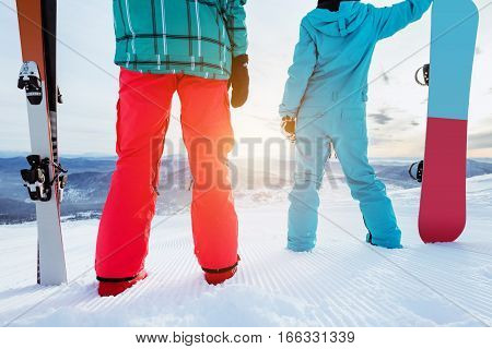 Couple of skier and snowboarder stands on ski slope at sunrise time. Skiing and snowboarding concept