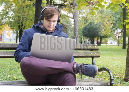 Young man with laptop in the park Selective focus and small depth of field lens flare