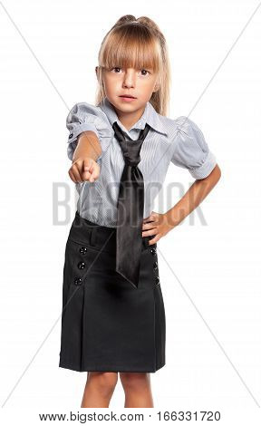 Portrait of little school girl pointing finger to you, isolated on white background. Serious child pointing at camera choosing you.