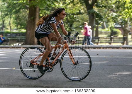 New York, September 17, 2016: A young woman is riding a bicycle in Central Park.
