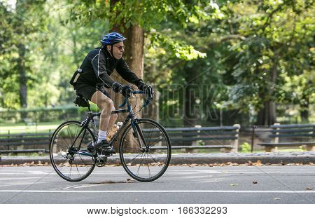 New York, September 17, 2016: An elderly man riding a bicycle in Central Park.
