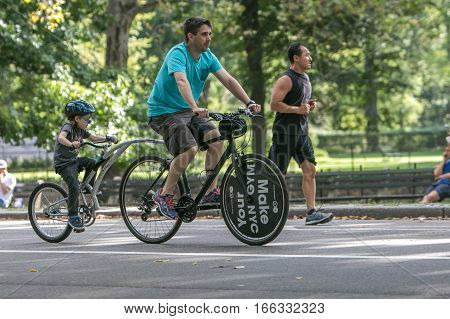 New York, September 17, 2016: A man and his son are riding in Central Park.