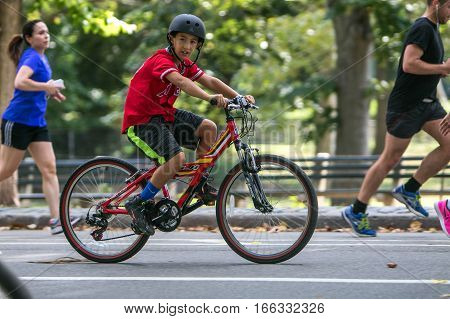 New York, September 17, 2016: A kid is riding his bicycle in Central Park.