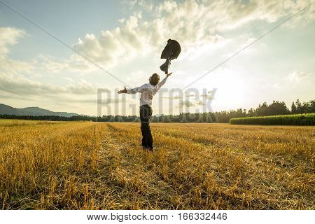 Scenic rear view of liberated businessman in field throwing jacket in air with sunshine and cloudscape background.