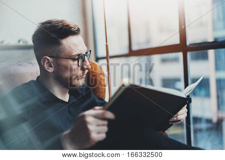 Attractive stylish businessman reading black book while sitting in vintage chair at his modern office.Young man relaxing after work day.Panoramic windows on blurred background.Horizontal, film effect