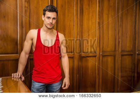 Sexy handsome young man standing, wearing red tank-top in his bedroom against wooden wardrobe door