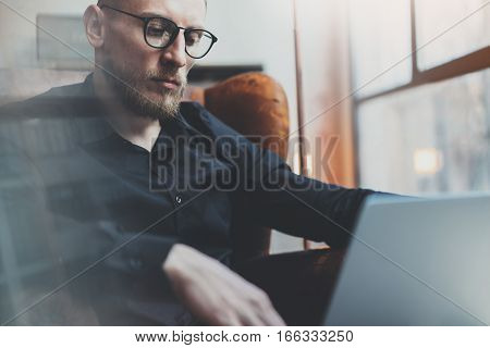 Sad bearded businessman working in modern loft office. Man using contemporary notebook while sitting in vintage chair. Panoramic windows on the blurred background. Horizontal, flare effect