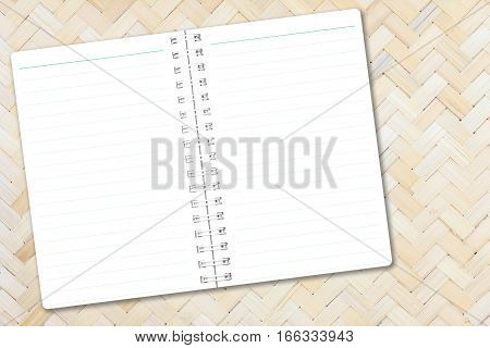 Open notebook paper with line on bamboo weave background for design with copy space for text or image.