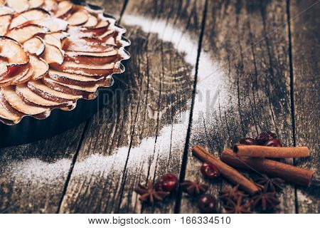 Apple pie tart on the rustic wooden background. Ingredients - apples and cinnamon .