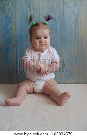 Adorable Baby Girl with  Sitting on a wooden floor
