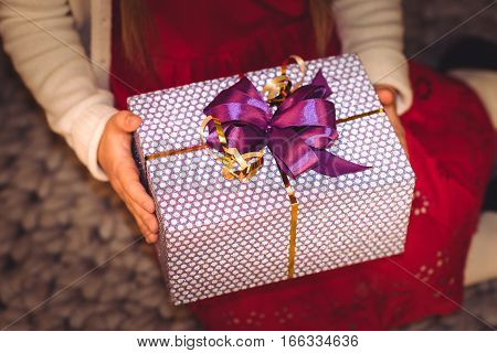 Partial view of girl holding gift box